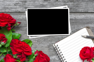 blank photo frame with red rose flowers bouquet and lined notebook