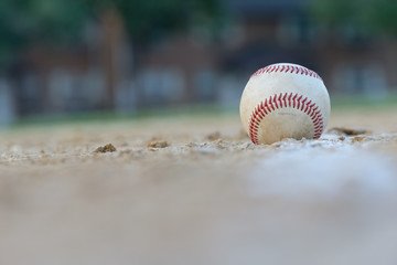 A baseball sits right on the foul line on a sandy baseball field