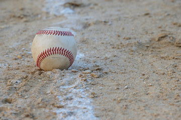 Baseball sits on the foul line on sandy lot
