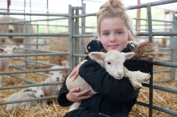 Girl sitting and holding a little lamb