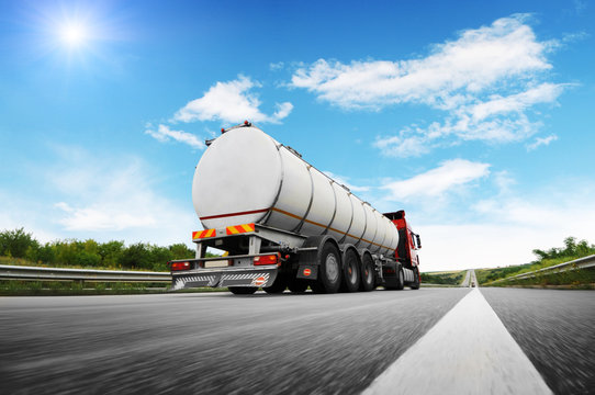 Rear view of big metal fuel tanker truck in motion shipping fuel against sky