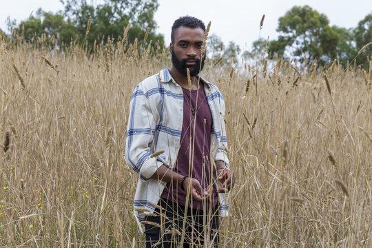 Young african male walking through long grass