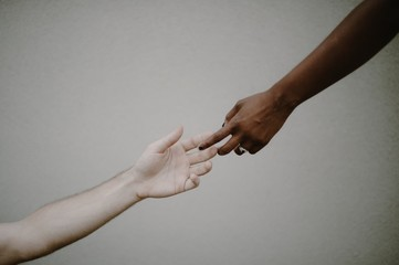 Reaching hands of black and caucasian race