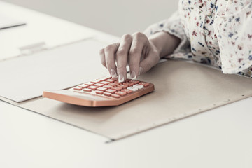 Female accountant calculating on orange desktop calculator