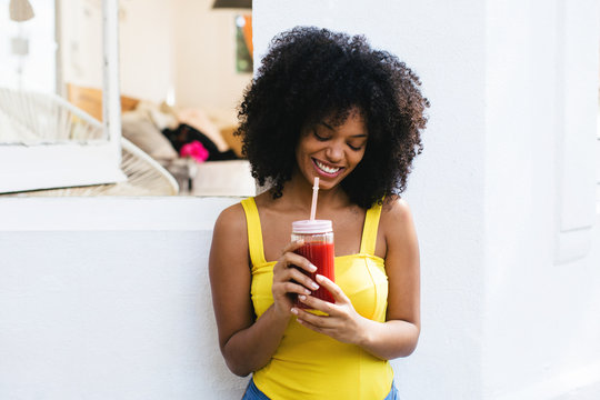 Afro woman drinking delicious smoothie in a backyard on a sunny summer day.