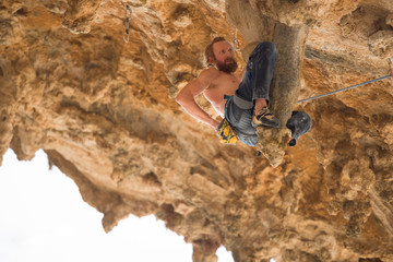 Portrait of man rock climber hanging on stalactite