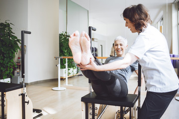 Woman Doing Legs Exercise With Therapist