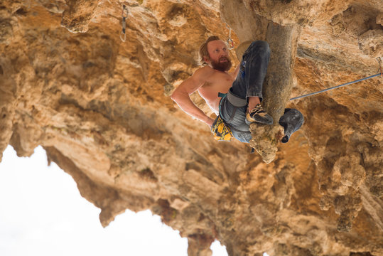 Portrait of man rock climber hanging on stalactite