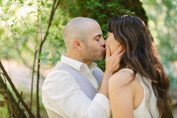 Groom Kissing Bride in Forest