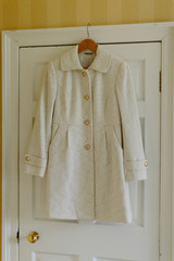 White Jacket with Gold Buttons Hanging on Door Frame