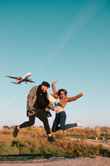 Couple jumping with a plane in the sky