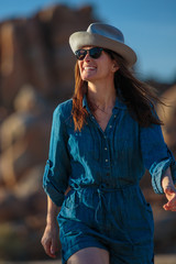 Woman wearing a hat and denim jumpsuit with sunglasses walking a