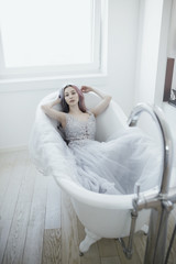 Young woman in a dress lying in a bathtub
