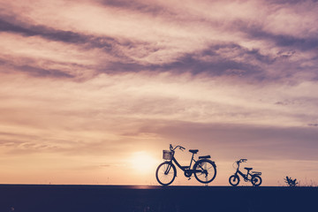 silhouette fo family bike on the sunset background