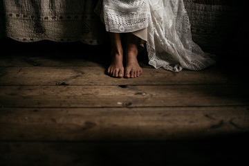 a barefoot bride sitting on a bed