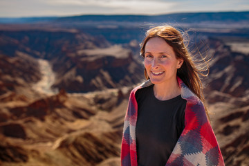 Beautiful woman standing above a canyon smiling