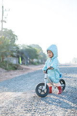 Asian boy about 1 year and 11 months with winter jacket is riding baby balance bike