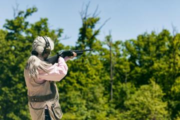 Shooting: Woman Aiming Shotgun Wearing Ear And Eye Protection