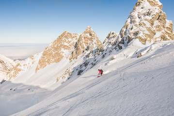 Man skiing off piste in mountains on a bright day