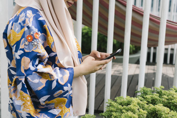 young woman in headscarf using smartphone