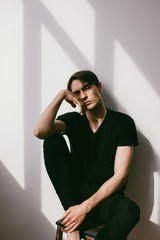 Vertical portrait of young handsome brunet in contrast lightning  and his shadow on white wall