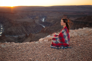 Woman with inner peace meditating at dawn dusk in mountains with