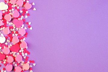 Side border of assorted Valentines Day sweets and candy over a pastel purple background