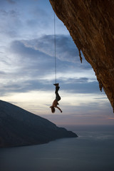 Person's silhouette hanging upside down from steep rock wall