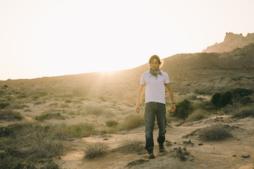 young man in used cowboy look walking through the desert at sunset