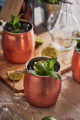 Moscow mule cocktails in copper mugs on a table.