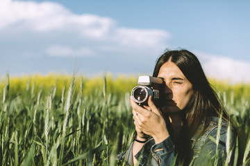 Woman recording with a  super 8 camera in wheat field at springtime