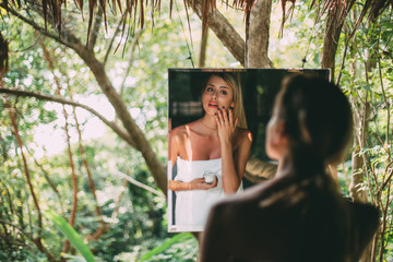 Woman looking in mirror in forest