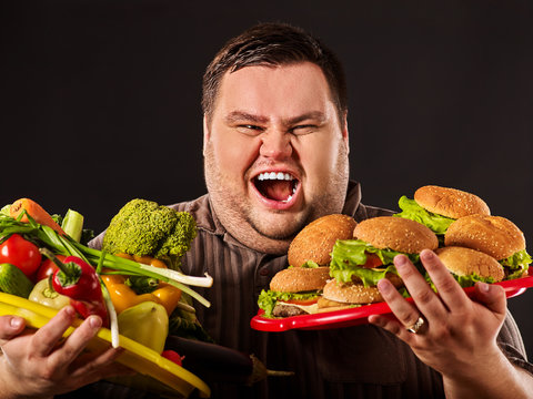 Diet fat man who makes choice between healthy and unhealthy food. Overweight male with hamburgers and vegetables trays trying to lose weight first time on black background. War for healthy food.