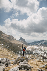 Woman doing gymnastics exercise while standing on the rock in the mountain