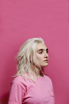 Young woman against pink background