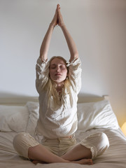 Woman doing yoga on bed