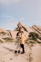 Tattooed couple standing in love in the desert