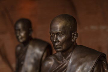 Buddhist monks statues symbol of peace and serenity at Wat Phu Tok temple, Thailand, ascetism and meditation, buddhist art work