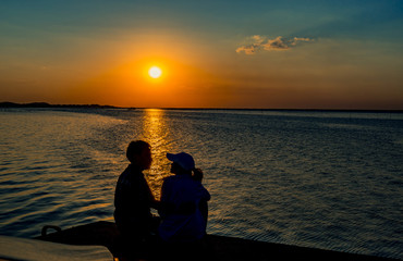 Silhouette of happiness couple in love sitting and kissing on the beach with orange and blue sky at sunset. Summer vacation and travel concept. Romantic young couple dating at seaside.