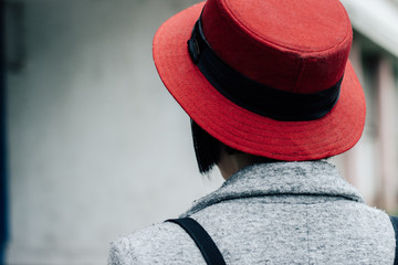 Portrait of a young female model with red hat using her phone in front of the building
