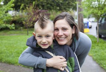 Mom hugs her freshly shaved boy before school