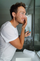 Man face cream beauty routine - facial skincare concept. Young adult in home bathroom looking at mirror putting moisturizer lotion in the morning taking care of dry skin. Moisturizing during winter.