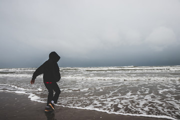 A little boy alone by the ocean