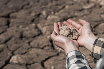 Hand woman holds a dry clay dirt with despair on dry soil background.