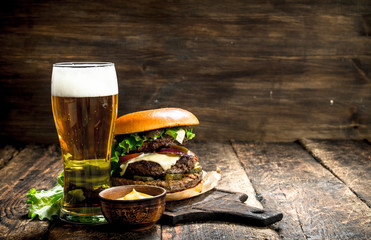 Fast food. A big burger with beef and a glass of beer.