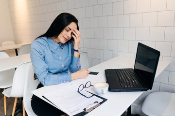 tired young girl freelancer in blue shirt working hard on laptop