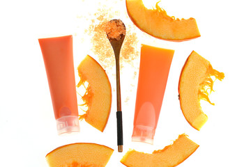 Pumpkin Mask.  mask with pumpkin extract in a plastic tube, sea salt with pumpkin extract and pieces of pumpkin isolated on white background. Set of organic cosmetics with pumpkin extract
