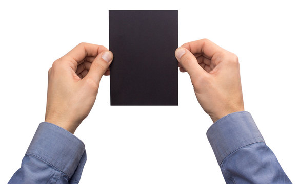 Mockup A6 empty blank black postcard vertically holds the man in his hand in shirt. Isolated on a white background