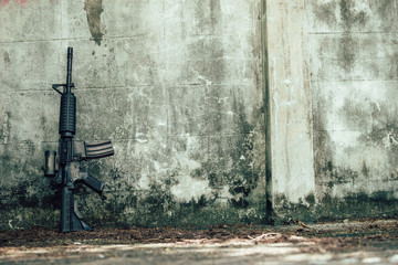 Assault rifle gun for the American military is placed beside the old wall.