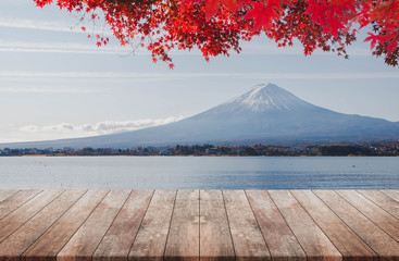 Wood table top on Mt Fuji in the morning background with red maple leaf in autumn - can used for display or montage your products.